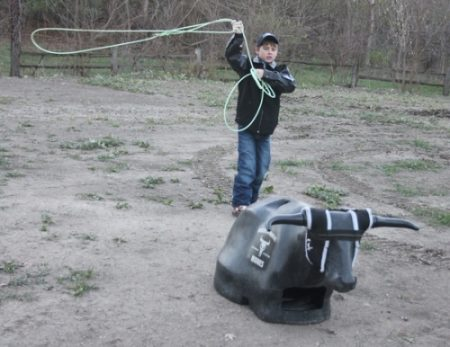 A boy is practicing lasso with a dummy steer head